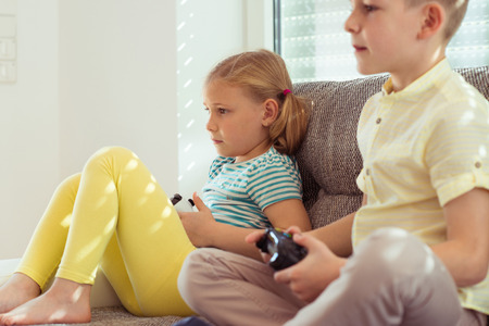 Photo pour Two happy children playing video games with console at home - image libre de droit