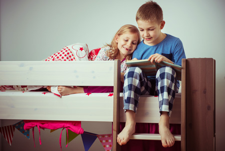 Photo pour Two happy sibling children reading book in bunk bed under blanket - image libre de droit