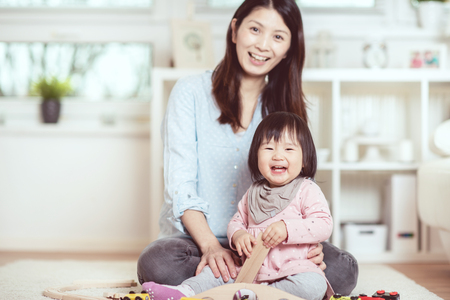 Foto de Pretty japanese woman playing with her cute laughing baby girl on the floor at home - Imagen libre de derechos