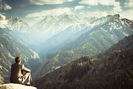 Foto de Image of a young businessman who sits on the top of the mountain and looks into the distance to the beautiful mountains, thinking about future plans. - Imagen libre de derechos