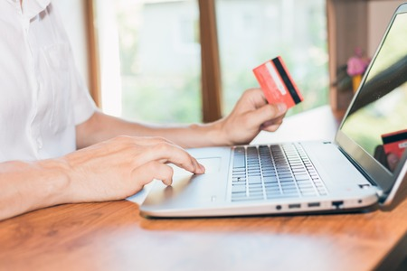 Photo for Concept of online payment by plastic card through the Internet Banking. Close-up of human hand for laptop and holding credit card, man is shopping indoor at home - Royalty Free Image