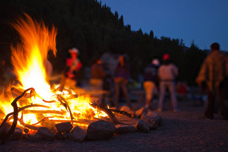 Foto de Image of a large campfire, around which people basking in the mountains at night - Imagen libre de derechos
