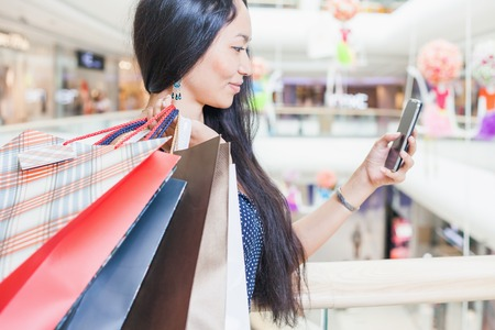 Foto de Fashion asian woman with a bag using mobile phone at big shopping center indoor. She received sms about sale and discount! Concept of shopping or shopaholic, sales and discounts at boutique - Imagen libre de derechos