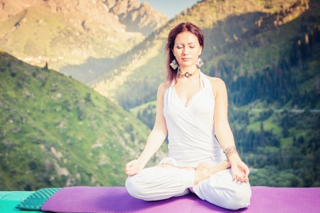 Photo pour Beautiful woman relaxing and meditating outdoor at swiss mountain. She sits at peak of mountain in lotus position and feel harmony of your body and nature. Healthy lifestyles concept of body and soul - image libre de droit