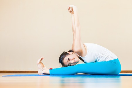 Photo pour Happy and beautiful asian woman doing exercise of yoga indoor at home. She looking at camera and smiling. You can maintain regular workouts at your home for free, be healthy and in good tonus! - image libre de droit
