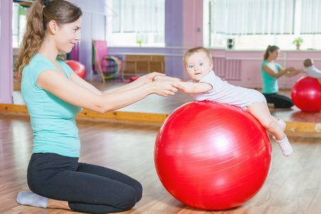 Foto de Mother with happy baby doing exercises with red gymnastic ball at fitness class. Concept of caring for the baby's health. - Imagen libre de derechos
