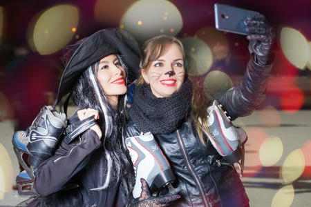 Two happy and funny girls make selfie on mobile phone. Dressed in cat and witch fancy dress. Horror and magic Halloween night. Holiday makeup. Girl holding ice skating boots