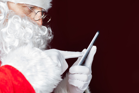 Photo for Santa Claus using a mobile phone at Christmas time. Santa typing message or sms to Elf or Dwarf. Luxory Cristmas gift or present for your good behavior! New Year. Copy space for disign, text - Royalty Free Image
