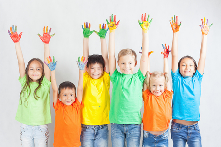 Foto de Group of multiracial funny children. Funny kids hands up. World Conference for Well-being of Children in Geneva, Switzerland, at June 1. Universal Children's Day on 20 November. - Imagen libre de derechos
