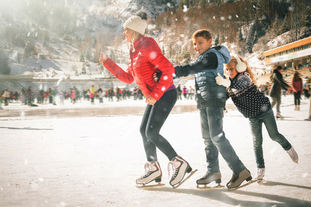 Photo pour Happy family outdoor ice skating at rink. Winter activities - image libre de droit