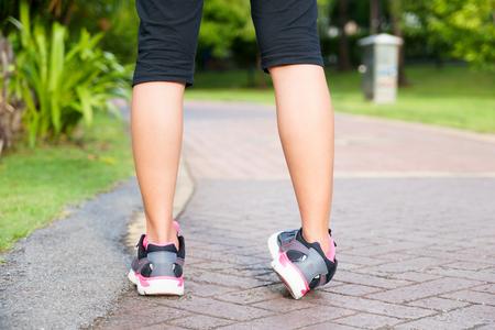 Foto de Sporty woman ankle sprain while jogging or running at park - Imagen libre de derechos
