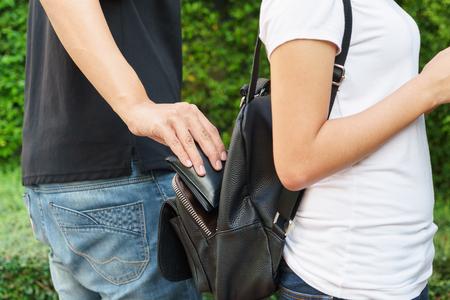 Foto de Thief trying to steal the wallet in the backpack in the park - Imagen libre de derechos