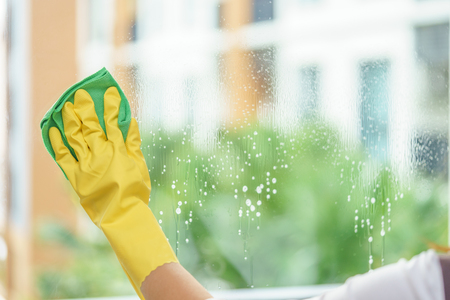 Foto de Woman housekeeper cleaning the mirror with green cloth. - Imagen libre de derechos