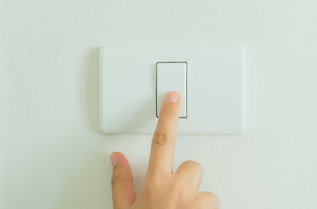 Photo for Close up of finger turning off on light switch on wall - Royalty Free Image