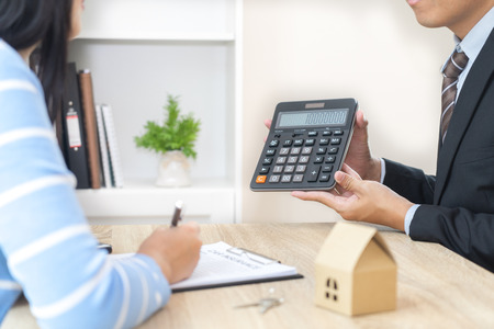 Photo pour Businessman showing the home price on calculator and customer ready to sign loan contract - image libre de droit