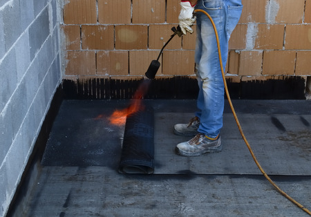 Worker preparing part of bitumen roofing felt roll for melting by gas heater torch flame