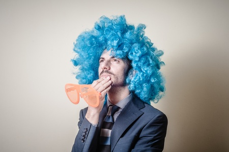 funny businessman with big orange glasses and blue wig on gray background