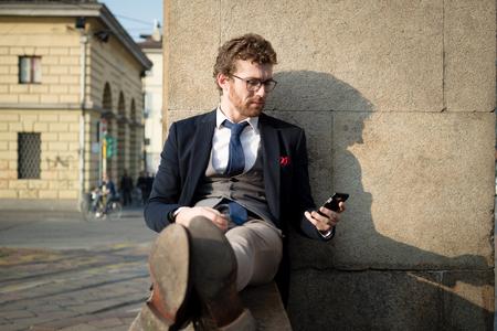 Foto de elegant attractive fashion hipster man on the phone in the city - Imagen libre de derechos
