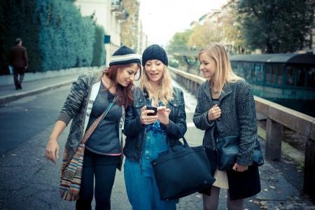 Foto de three friends woman on the phone in the street - Imagen libre de derechos