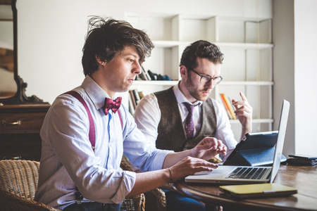 Foto de two young hipster stylish elegant men working with notebook and tablet at home  - Imagen libre de derechos