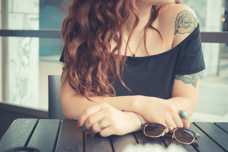 Foto de young beautiful hipster woman with red curly hair at the bar - Imagen libre de derechos