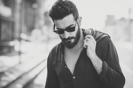 Photo pour young handsome attractive bearded model man in urban context - image libre de droit