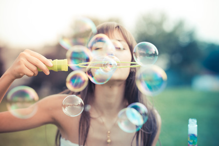 Foto de beautiful young woman with white dress blowing bubble in the city - Imagen libre de derechos