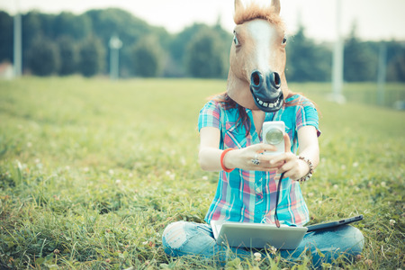 Foto de horse mask unreal hipster woman using technology in the park - Imagen libre de derechos