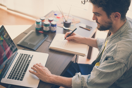 Foto de handsome hipster modern man designer working home using laptop at home - Imagen libre de derechos