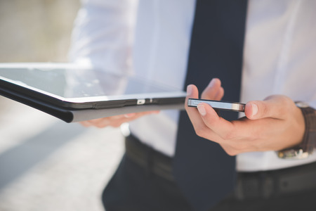 Foto de close up businessman man hand using tablet and smart phone device outdoor - Imagen libre de derechos