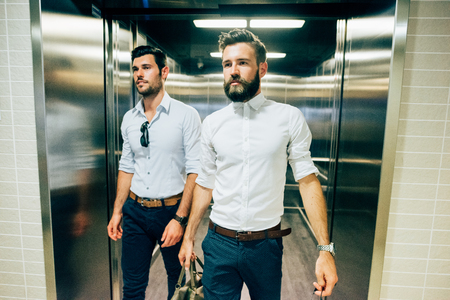 Photo pour Two young handsome black and blonde hair modern businessman exiting from a elevator, one holding a bag, both overlooking right - business, working, successful concept - image libre de droit