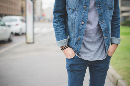 Photo for Cropped front view of young handsome alternative dark model man posing in town with hands in pocket - wearing gray shirt, jeans pants and jacket - Royalty Free Image