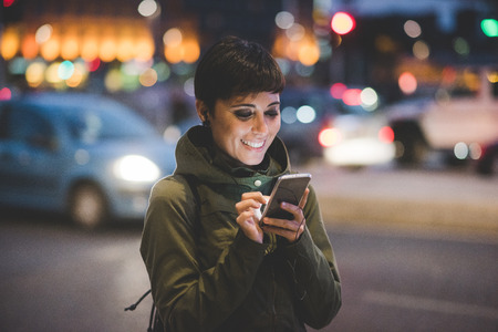 Foto de Half length of young handsome caucasian brown straight hair woman holding a smartphone looking down the screen in city night, face illuminated by screenlight - technology, communication concept - Imagen libre de derechos