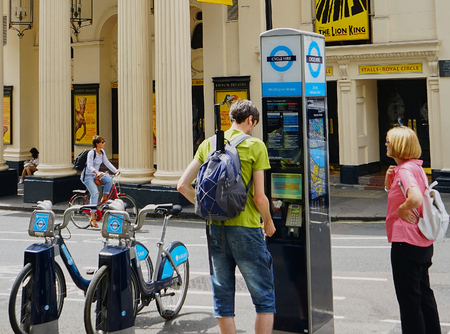 London, England - Aug 2015: City Bicycle Rental Depot being used by young man with backpack and ear buds.