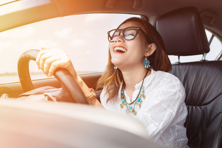 Photo for Asian woman driving a car in a happy mood. - Royalty Free Image