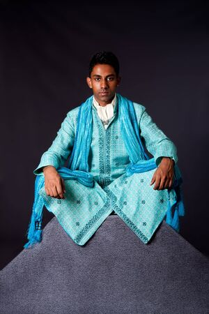 Beautiful authentic Indian hindu man in typical ethnic groom attire sitting in lotus position with legs crossed on top of rock. Bangali male wearing a light blue agua decorated Dhoti with shawl.