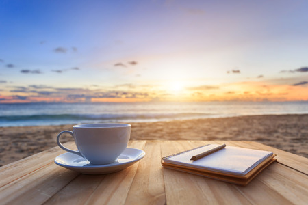 Photo for Close up coffee cup on wood table at sunset or sunrise beach - Royalty Free Image