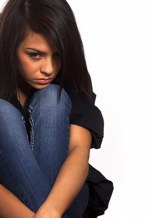 Sad young woman crouching on floor (acting)