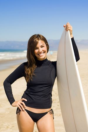 Beautiful young woman at the beach with surfboard