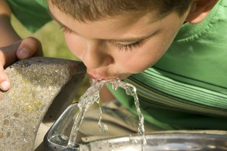Little boy drinking water from a fountain