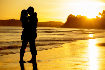 Photo pour Silhouette of a couple on the beach at sunset - image libre de droit