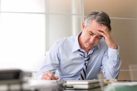 Foto de Frustrated stressed business man in an office - Imagen libre de derechos