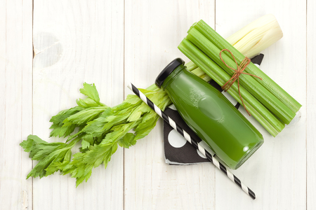 Photo for Vegetable juice in bottle with celery stalk on white wood background - Royalty Free Image
