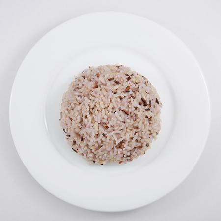 Foto de The cooked brown rice on the white plate. - Imagen libre de derechos