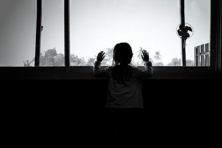 Foto de Asian child girls are standing in the dark, looking out the window,sad mood, black and white tones. - Imagen libre de derechos