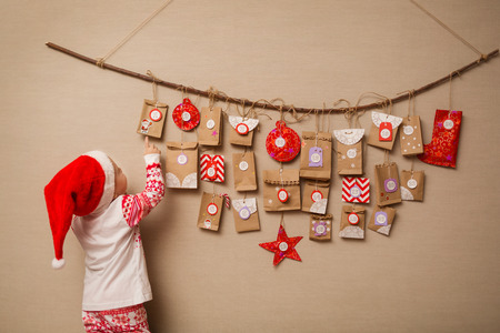 Photo for child looks at the advent calendar. Baby girl in a Christmas hat and pajamas shows on first gift - Royalty Free Image
