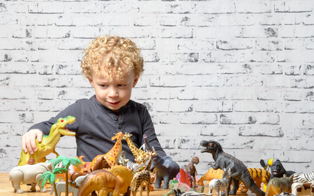Photo pour a little child plays with toys animals and dinosaur - image libre de droit