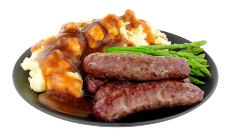 Photo pour Fried venison sausages meal with mashed potatoes and asparagus on a black plate isolated on a white background - image libre de droit