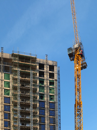 Photo pour a tall yellow construction crane working on a large hight rise concrete building with scaffolding against a blue sky - image libre de droit