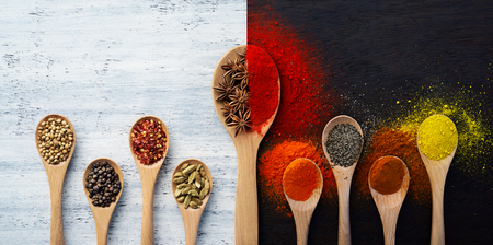 Wooden spoon filled with spices, herbs, powders and ground spices